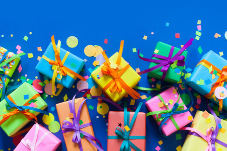 色の多くの贈り物はうそをつくし、青い背景の上に立ちます。 写真素材