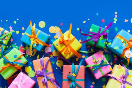 Muchos regalos coloreados mienten y se colocan en un fondo azul. Foto de archivo - 87016402