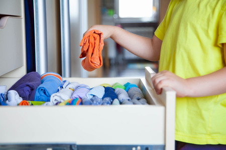 skirts: The child puts his clothes on. The boy pulls the T-shirt out of the closet. Stock Photo