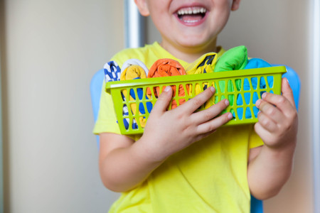 skirts: The child keeps his things. The boy puts the T-shirts in a drawer. Stock Photo