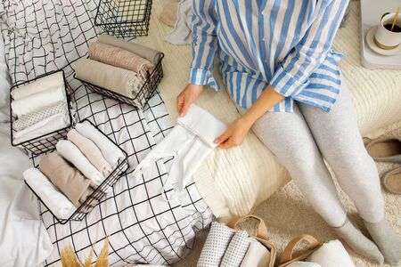 Unidentified slim woman neatly tidies household Stock Photo