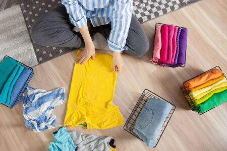 Top view a young woman in casual clothes stacks things, sorting them by colors and folding them into a metal mesh basket. Concept of smart tidy and cleanliness in the house Standard-Bild