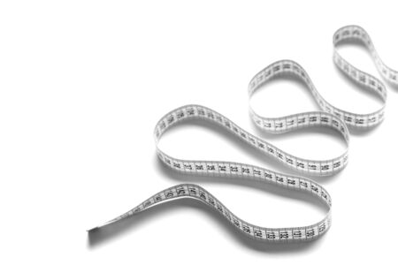 The figure is spiral of a centimeter tape. Isolate measuring tape on a white background. Stock Photo
