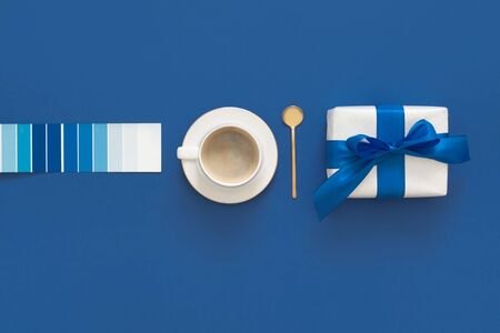 Classic Blue. Color of the Year 2020. Top view of workspace with coffe, gift and glasses and copy space on colored blue background. Flatlay minimalism Imagens