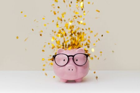 Pink piggy bank with birthday cap on beige background