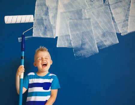 Classic Blue. Color of the Year 2020. A child is painting a blue wall. Imagens