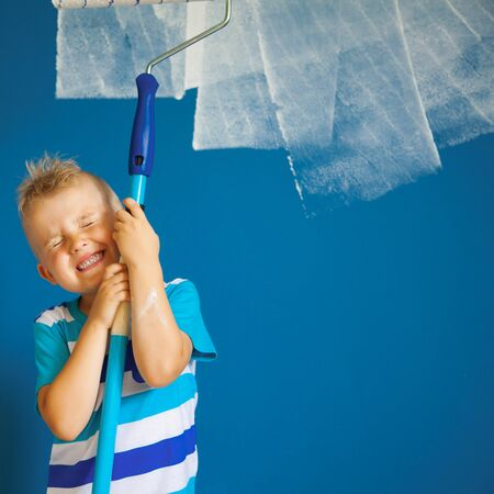 Classic Blue. Color of the Year 2020. A child is painting a blue wall.