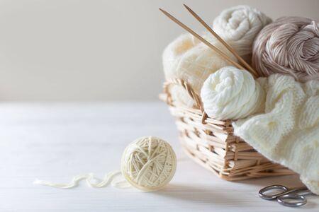 Yarn, knitting needles, wicker basket. White background.