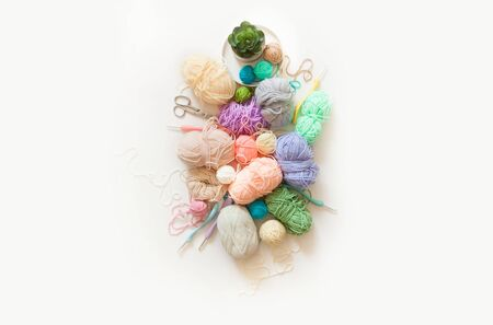 Colored yarn on a white background. Crochet hooks, scissors, and accessories.