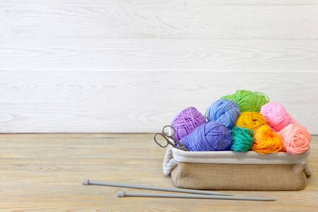 Colored yarn. Knitting needles. Wooden background.