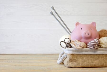 Colored yarn. Knitting needles. Pig piggy bank with glasses. Wooden background.