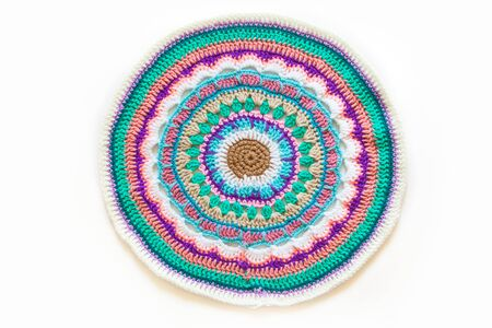 Round mandala crocheted from colored yarn. White background. Stockfoto