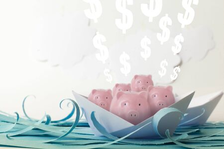 Many pink piggy banks and euro floating on paper boats on blue paper sea Stock Photo