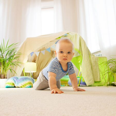 Baby toddler crawling on the carpet on the background of a childrens tent Stock Photo