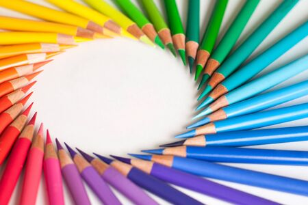 Crayons - colored pencil set loosely arranged on white background. Round frame.