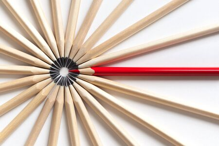 Top view of a red pencil tends to fall into a circle of gray pencils lying on a white background. Concept of unsuitable standout employee in an office team. Eccentric concept 免版税图像
