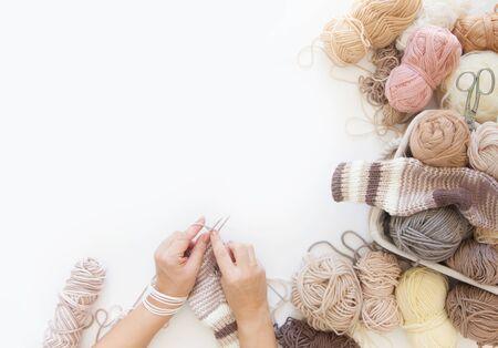 Women crochet and knitting from beige yarn. View from above. Woolen warm socks