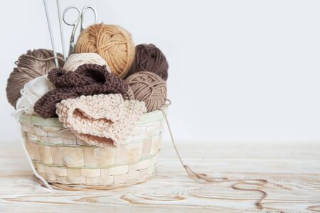 Neutral beige, brown, white yarn in a wicker basket. Yellow background. Aged wood. Needles, scissors. Фото со стока