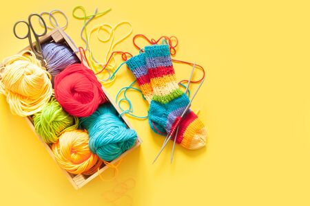 Knitting for children. Bright striped rainbow socks. Colored yarn. Yellow background. Wicker basket.