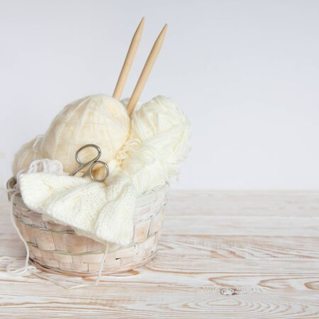 Neutral white yarn in a wicker basket. White background. Aged wood. Needles, scissors. Фото со стока
