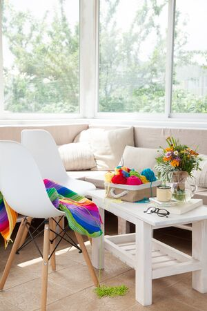 Bright colored yarn for knitting in a basket. A bouquet of wild flowers. Glasses, chairs. White furniture.