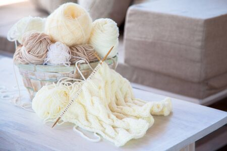 Neutral beige, brown, white yarn in a wicker basket. White background. Aged wood.