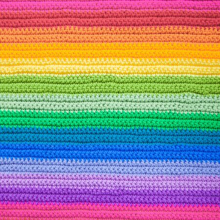 Crocheted crocheted color, bright, rainbow knitted fabric. Striped blanket. Female handicraft knitting.