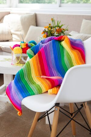 Colorful, bright, iridescent plaid, blanket. Crochet. Knitting yarn in a basket on a white armchair Фото со стока