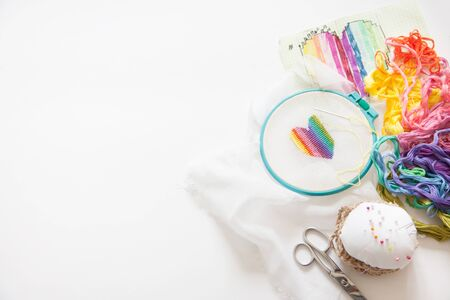 A multicolored, rainbow-colored heart is embroidered with a cross on a white canvas. Cross-stitch. Basket with threads floss. Scissors. Фото со стока