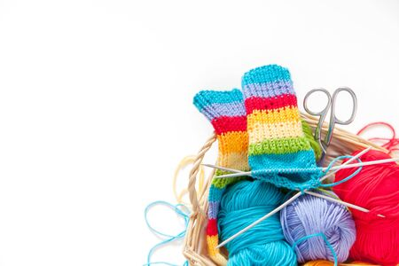 Knitting for children. Bright striped rainbow socks. Colored yarn. White background. Wicker basket. Stock Photo