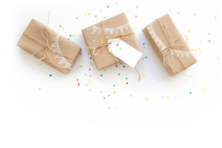 White gift box. Drawing of a white garland, flags. White background. Confetti.