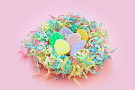 Sweets for celebrate Easter. Gingerbread in shape of easter bunny and easter eggs. White and color background top view copy space