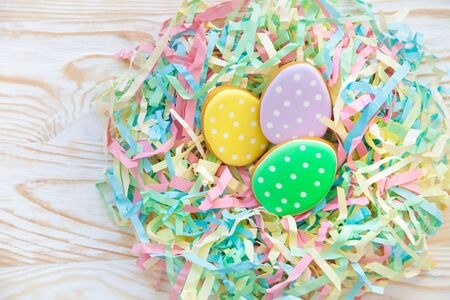Easter homemade gingerbread cookie. Birds nest Easter made from colored paper. The background is aged light wood. 免版税图像