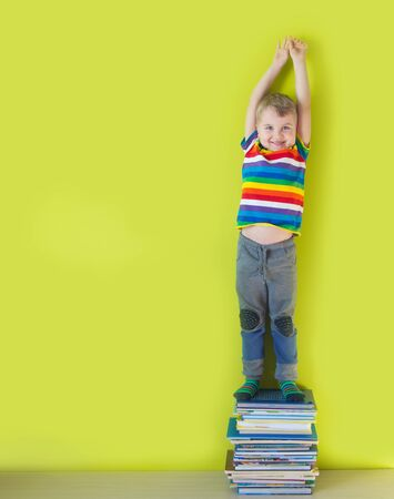 A joyful smiling child is standing on a stacked of childrens books. Green background.