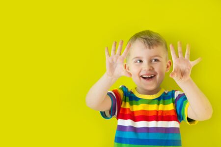 A joyful, cheerful, smiling child stretched out his palms forward. Green background.