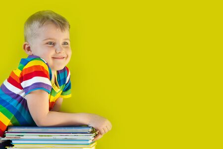 The child holds a large stacked of childrens books in his hands. Green background.