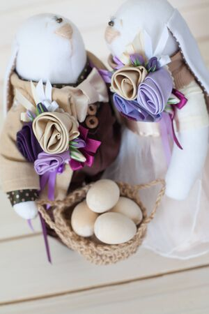 Two handmade rabbits hold a basket with eggs. White wood background. Beige and lilac.