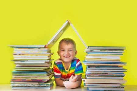 The child sits inside a house made of childrens books. Green background. A lot of books.