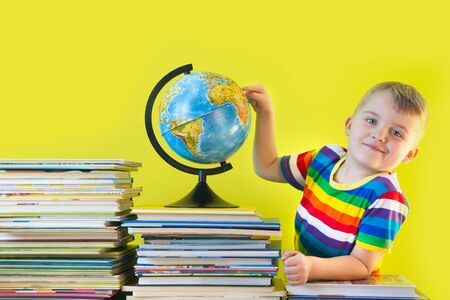 The boy sits next to the childrens books and the globe. Green background.