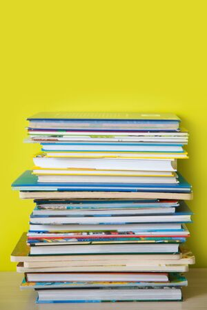 Many childrens books are stacked on top of each other. Green background.