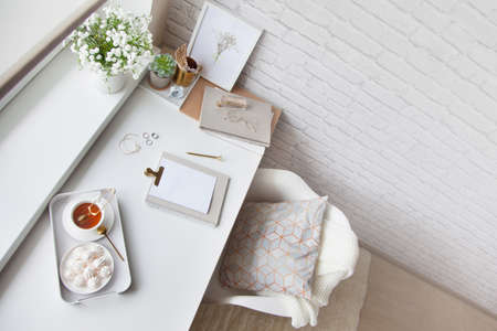 Work table near the window in the Scandinavian Nordic style. Female work and home office concept. White and gold office. Flowers in a vase and rings, bracelets on the table.