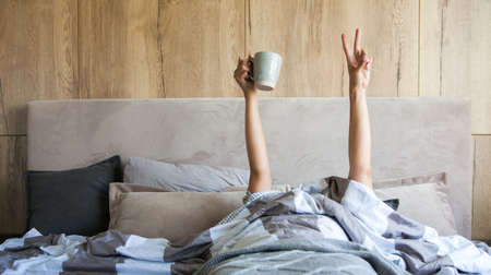 Womans hand with a cup of coffee in bed, the concept of the beginning of a new day, good morning