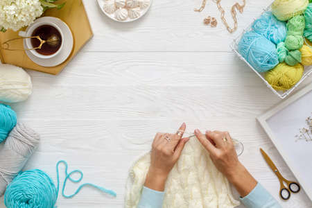 Female hands knitting with white wool, on a wooden background, top view. Handicraft accessories, tea, diary and hydrangea flowers.