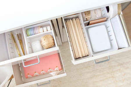The gold stationery is neatly arranged in white containers in the drawers of the nightstand. Storage and tidying up the workplace.