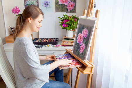 Young smiling caucasian beautiful girl artist paints a picture