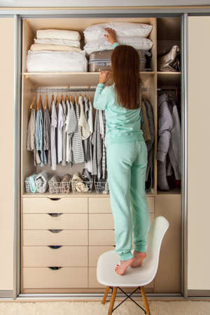 Young woman organizes storage on the top shelf of a wardrobe. Suitcase and pillows on the mezzanine. Clothes storage.