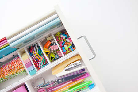 Female white workplace. A method for storing stationery neatly. Stylish colored pens, stapler, pencils.