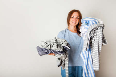Caucasian housewife holding heap of dirty clothing.
