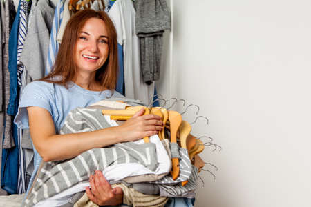 Happy caucasian woman holding bunch of wooden hangers with sorted cotton and wool shirts.