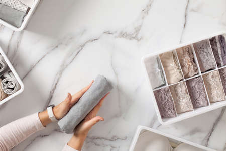 Woman hands neatly folding underwears and sorting in drawer organizers on white marble background.